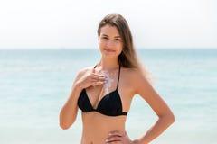Η ελκυστική γυναίκα ισχύει sunblock στο στήθος της με τα δάχτυλα στο υπόβαθρο θάλασσας στοκ φωτογραφίες με δικαίωμα ελεύθερης χρήσης