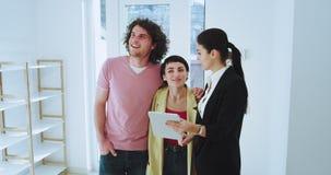 Η ελκυστική γυναίκα κτηματομεσιτών με ένα μεγάλο χαμόγελο που παρουσιάζει νέο σύγχρονο σπίτι σε μια νέα οικογενειακή μάγισσα είνα απόθεμα βίντεο