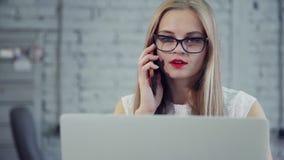 Η ελκυστική γυναίκα με τα κόκκινα χείλια κάθεται και εργάζεται στο νέο πρόγραμμα χρηματοδότησης στον πίνακα γραφείων απόθεμα βίντεο
