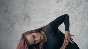 η ελκυστική γυναίκα στέκεται και εξετάζει τη cameraBeautiful νέα γυναίκα με τη ρόδινη τρίχα, να χορεψει επαγγελματικά σαγηνευτική απόθεμα βίντεο
