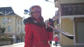 Η ελκυστική γυναίκα στέκεται κοντά στα σπίτια κρατώντας την κάνει σκι προς τα κάτω πρίν κάνει σκι απόθεμα βίντεο