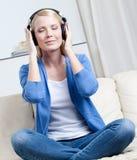 Η ελκυστική γυναίκα στα ακουστικά ακούει τη μουσική Στοκ φωτογραφία με δικαίωμα ελεύθερης χρήσης