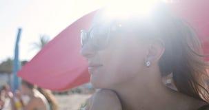 Η ελκυστική γυναίκα στα γυαλιά ηλίου κάνει ηλιοθεραπεία στην παραλία φιλμ μικρού μήκους