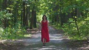 Η ελκυστική γυναίκα στο κόκκινο φόρεμα περπατά το δάσος, θηλυκό στην εξάρτηση βραδιού, υψηλά τακούνια φιλμ μικρού μήκους