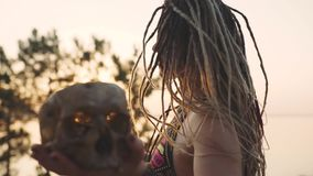 Η ελκυστική γυναίκα χίπηδων χορεύει και δημιουργεί με ένα ανθρώπινο κρανίο Γυναίκα στην εικόνα μιας μάγισσας στο ηλιοβασίλεμα ή τ απόθεμα βίντεο