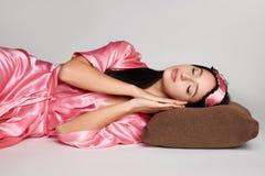 Η ελκυστική γυναίκα brunette στη ρόδινη εσθήτα βάζει στο μαξιλάρι με τις προσοχές ιδιαίτερες στο πάτωμα με το blindfold Στοκ Εικόνα