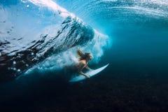 Η ελκυστική γυναίκα surfer βουτά υποβρύχιος, κάτω από το κύμα βαρελιών στον μπλε ωκεανό στοκ φωτογραφίες