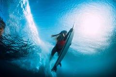 Η ελκυστική γυναίκα surfer βουτά υποβρύχιος με το κατώτερο κύμα βαρελιών στοκ εικόνα