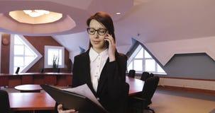 Η ελκυστική επιχειρησιακή γυναίκα στα γυαλιά μιλά στο κινητό τηλέφωνό της σε ένα σύγχρονο γραφείο φιλμ μικρού μήκους