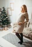 Η ελκυστική ευτυχής έγκυος γυναίκα με την ξανθή τρίχα την αγγίζει tummy στο άσπρο σύγχρονο δωμάτιο με το χριστουγεννιάτικο δέντρο Στοκ Φωτογραφία