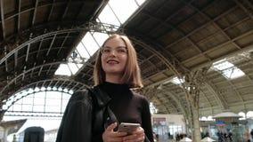 Η ελκυστική κοκκινομάλλης νέα γυναίκα με το σύντομο κούρεμα, που φορά τα γυαλιά και το μαύρο σακάκι δέρματος στέκεται σε όμορφο απόθεμα βίντεο