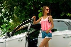 Η ελκυστική κυρία μόδας στα γυαλιά και τα κοντά σορτς ανοίγει την πόρτα αυτοκινήτων Στοκ Εικόνες