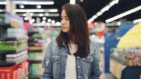 Η ελκυστική κυρία περνά από το διάδρομο στην υπεραγορά με το κάρρο αγορών εξετάζοντας τα ράφια με τα φωτεινά αγαθά Αγορές απόθεμα βίντεο