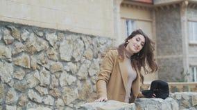 Η ελκυστική, λαμπρή γυναίκα στέκεται σε ένα μπαλκόνι πετρών σε ένα ιστορικό κτήριο κάπου στην Ευρώπη Το κορίτσι θαυμάζει απόθεμα βίντεο