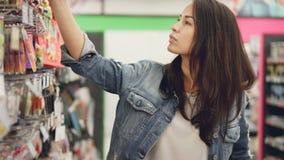 Η ελκυστική νέα γυναίκα αγοράζει τα κεριά γενεθλίων στην υπεραγορά, παίρνει τα αγαθά, εξετάζει τα και συγκρίνει απόθεμα βίντεο