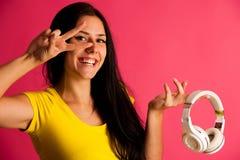 Η ελκυστική νέα γυναίκα ακούει μουσική πέρα από το ρόδινο υπόβαθρο Στοκ εικόνα με δικαίωμα ελεύθερης χρήσης