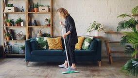 Η ελκυστική νέα γυναίκα καθαρίζει το καθιστικό που το πάτωμα που κάνει τα οικιακά Όμορφο διαμέρισμα ύφους σοφιτών με απόθεμα βίντεο