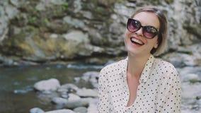 Η ελκυστική νέα γυναίκα με την ξανθή πλεγμένη τρίχα χαμογελά ευρέως και χαρωπά στη κάμερα στα σκοτεινά γυαλιά ηλίου, κυρία στο λε φιλμ μικρού μήκους