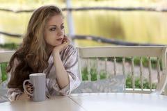 Η ελκυστική νέα γυναίκα που ντύνεται στο μετάξι peignoir πίνει έναν ομο Στοκ Εικόνες