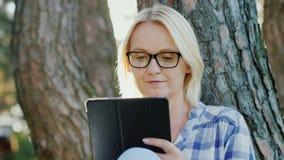 Η ελκυστική νέα γυναίκα στα γυαλιά χρησιμοποιεί μια ταμπλέτα Κάθεται σε ένα πάρκο κοντά σε ένα δέντρο, όμορφο φως πριν από το ηλι φιλμ μικρού μήκους