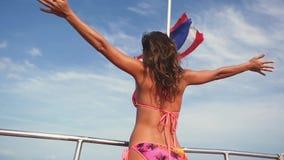 Η ελκυστική νέα γυναίκα στο μπικίνι στέκεται με τα όπλα στο ανώτερο κατάστρωμα του πλοίου κίνηση αργή απόθεμα βίντεο