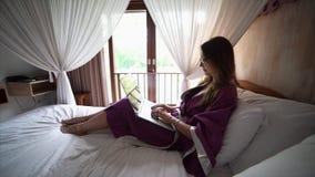 Η ελκυστική νέα γυναίκα στο μπουρνούζι κουβεντιάζει στο διαδίκτυο φιλμ μικρού μήκους