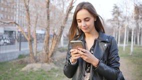 Η ελκυστική νέα γυναίκα στο πάρκο χρησιμοποιεί το τηλέφωνο περίπατος μέσω του κέντρου πόλεων το βράδυ Περίπατοι νέοι γυναικών στο απόθεμα βίντεο