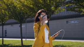 Η ελκυστική νέα επιχειρηματίας στα γυαλιά ηλίου πίνει τον καφέ ενώ αυτή που στέλνει ένα μήνυμα στον υπολογιστή ταμπλετών υπαίθρια απόθεμα βίντεο