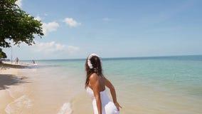 Η ελκυστική νέα ευτυχής γυναίκα στα τρεξίματα στεφανιών άσπρων φορεμάτων και λουλουδιών κατά μήκος seacoast χωρίς παπούτσια και απόθεμα βίντεο