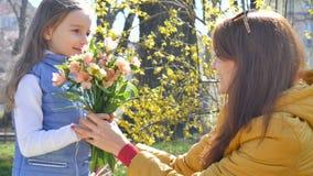 Η ελκυστική νέα μητέρα λαμβάνει μια ανθοδέσμη των ζωηρόχρωμων λουλουδιών από την λίγη ξανθή κόρη E φιλμ μικρού μήκους