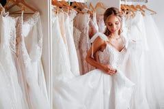 Η ελκυστική νέα νύφη χαμογελά επιλέγοντας το γαμήλιο φόρεμα στοκ φωτογραφία