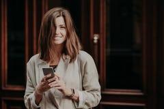 Η ελκυστική νεολαία που χαμογελά τα θηλυκά μηνύματα κειμένων blogger στους οπαδούς, έχει το χρόνο αναψυχής, που είναι στην καλή δ στοκ φωτογραφία με δικαίωμα ελεύθερης χρήσης