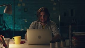 Η ελκυστική συγκεντρωμένη εργασία εργαζομένων γραφείων σκληρά στο γραφείο του αργά τη νύχτα, πίνει το τσάι και προγραμματισμός κά απόθεμα βίντεο