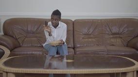 Η ελκυστική συνεδρίαση γυναικών αφροαμερικάνων στον καναπέ και επρόκΠφιλμ μικρού μήκους