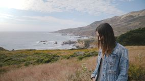 Η ελκυστική χαμογελώντας νέα ευτυχής γυναίκα εξετάζει τη κάμερα στην επική μεγάλη ωκεάνια ακτή Sur που καλύπτεται με τα πολύβλαστ απόθεμα βίντεο