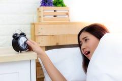 Η ελκυστική όμορφη γυναίκα εξετάζει το ξυπνητήρι και τον εργαζόμενο στοκ φωτογραφία