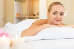 Η ελκυστική όμορφη γυναίκα καθορίζει στο κρεβάτι στο σαλόνι SPA Η όμορφη νέα γυναίκα εξετάζει τη κάμερα και παίρνει τη ικανοποιημ στοκ φωτογραφία