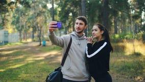Η ελκυστικοί γυναίκα και ο άνδρας κάνουν τη σε απευθείας σύνδεση τηλεοπτική κλήση με το smartphone στο πάρκο μετά από την αθλητικ φιλμ μικρού μήκους