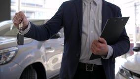 Η εμπορία αυτοκινήτων, αρσενικό διευθυντών αυτοκινήτων κρατά στα κλειδιά χεριών στο νέο αυτοκίνητο για την πώληση στην αίθουσα εκ απόθεμα βίντεο