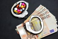 Η εμπορία ναρκωτικών είναι παράνομη, με τα χάπια ή τα ναρκωτικά στις χειροπέδες στα ευρο- τραπεζογραμμάτια στοκ εικόνα