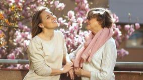 Η ενήλικες μητέρα και η κόρη μιλούν τη στάση σε ένα μπαλκόνι σε ένα υπόβαθρο ενός magnolia άνθησης Ημέρα των διεθνών γυναικών απόθεμα βίντεο