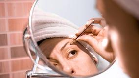 Η ενήλικη γυναίκα διορθώνει τα φρύδια και το κοίταγμα στον καθρέφτη φιλμ μικρού μήκους