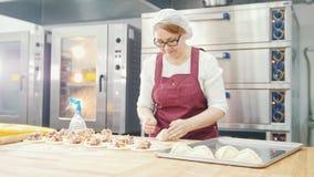 Η ενήλικη γυναίκα στα ποτήρια ψήνει τα κέικ στο αρτοποιείο απόθεμα βίντεο