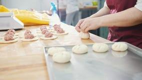 Η ενήλικη γυναίκα ψήνει και διαμορφώνοντας τις πίτες κρέατος στο αρτοποιείο φιλμ μικρού μήκους