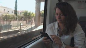 Η ενήλικη γυναίκα brunette κουβεντιάζει από το smartphone, στέλνοντας sms, καθμένος στο τραίνο φιλμ μικρού μήκους