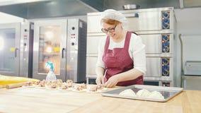 Η ενήλικη καλή χαμογελώντας γυναίκα ψήνει και διαμορφώνοντας τα κέικ στο αρτοποιείο φιλμ μικρού μήκους