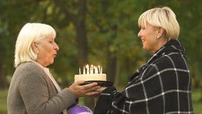 Η ενήλικη κόρη επιθυμεί την παλαιά μητέρα χρόνια πολλά, που δίνει το κέικ, οικογενειακός εορτασμός απόθεμα βίντεο