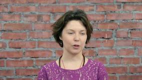 Η ενήλικη γυναίκα λέει κάτι στον άνδρα πίσω από τη κάμερα ρίψη κόκκινο με την άσπρη ένωση waggle φιλμ μικρού μήκους
