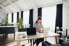 Η ενήλικη γυναίκα κάθεται σε έναν καφέ και ξαναγράφει τις πληροφορίες από το τηλέφωνο στο lap-top συγκρίνοντας το ελκυστικό θηλυκ Στοκ Φωτογραφία