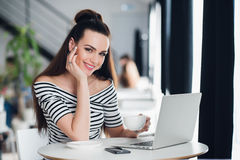 Η ενήλικη ελκυστική επιχειρηματίας εργάζεται στο lap-top της σε έναν καφέ, η χαμογελώντας νέα γυναίκα χρησιμοποιεί ένα lap-top στ Στοκ φωτογραφία με δικαίωμα ελεύθερης χρήσης